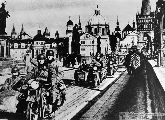 """The Occupation of Prague: A Motorcycle Division on the Charles Bridge (March 15, 1939)   While Hitler was declaring his peaceful intentions after the Munich Agreement, he was also planning the """"liquidation of rump Czechoslovakia."""" Here, Hitler's primary objectives included improving Germany's strategic and economic position to better prepare for a later attack on Poland and the Soviet Union."""