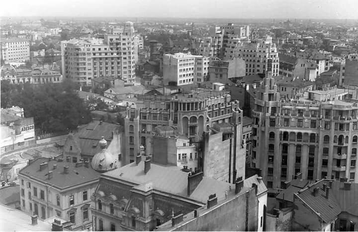 """Vedere de pe Palatul Telefoanelor spre cele doua hoteluri care incadreaza """"Regala"""".  In plan apropiat o aripa a """"Continentalului"""" iar in departare, intunecata, Biserica Italiana."""
