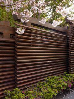 Louvre-achtig tuinscherm waarbij de planken schuin in de paal geplaatst zijn.