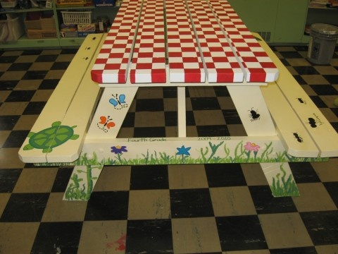 Picnic table painted by the students with grass, ladybugs, ants, etc.