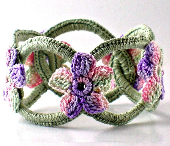Dieses Armband besteht aus fünf 5 feine häkeln Thread ineinander greifende Ringe aus Kettenhemd zu simulieren und akzentuiert mit kleinen gehäkelten Blüten.  Es ist tatsächlich ein Armreif, die über Ihre Hand Rutschen wird. Es ist dehnbar, so dass es die meisten kleinen bis mittleren Frauen Hände passen. Es misst 8 ¼ Zoll (21 cm) herum und Wille reichen bis über den breitesten Teil Ihrer Hand passen. Um festzustellen, ob es Ihnen passt, machen Sie eine Faust und Messen Sie den Abstand…