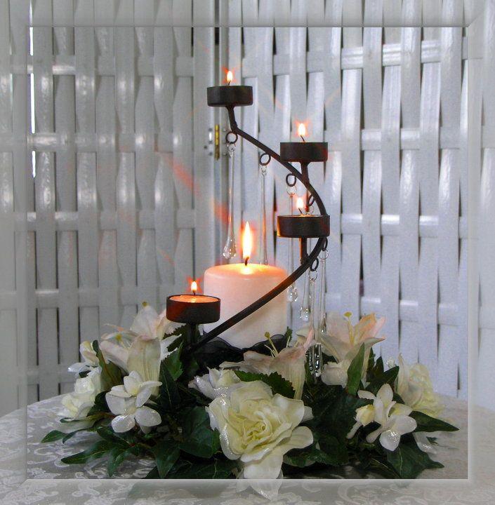 Centro de mesa con flores y velas sobre herrería