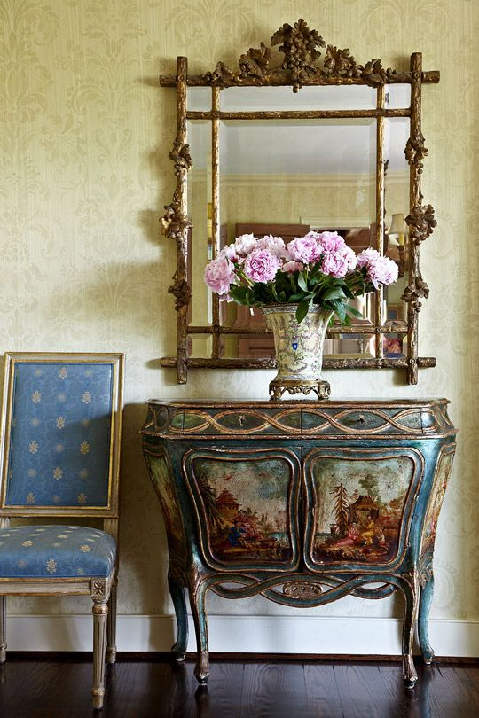 The dining room in JoBeth Williams' Spanish-Style Home features a  painted commode and giltwood mirror which complement the hand-stenciled, damask pattern walls with strié.