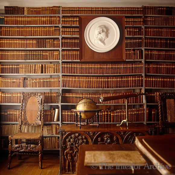 An antique globe and telescope stand on a carved chest in this library which is lined with leather-bound books