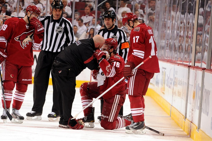 APRIL 29: Rostislav Klesla #16 of the Phoenix Coyotes is checked out by head athletic trainer Jason Serbus after being hit in the face with a puck against the Nashville Predators in Game Two of the Western Conference Semifinals during the 2012 NHL Stanley Cup Playoffs at Jobing.com Arena on April 29, 2012 in Glendale, Arizona. (Photo by Norm Hall/NHLI via Getty Images)