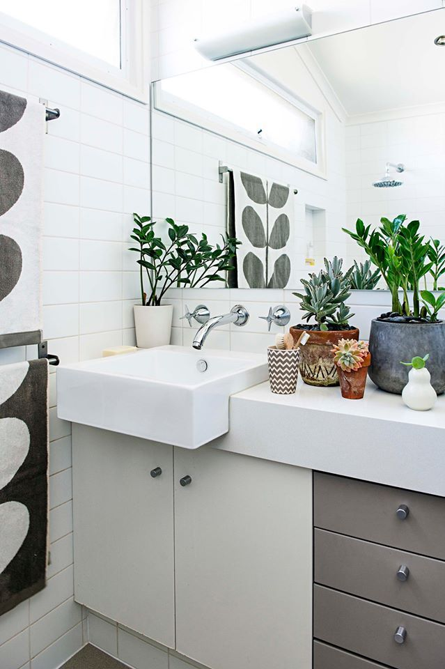 semi-recessed rectangular basin sits atop Ikea kitchen cupboards; subway tile; Orla Kiely towels