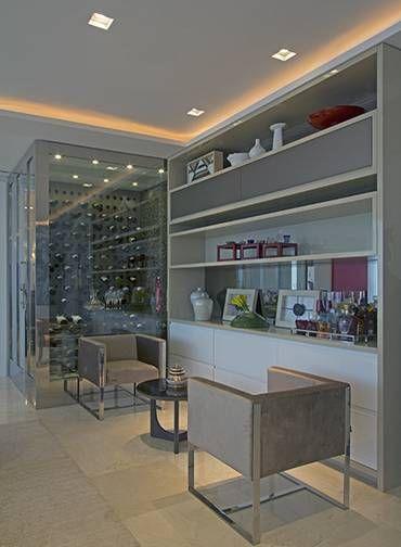 A adega do projeto de Jóia Bergamo é uma espécie de segundo ambiente da sala. Com paredes envidraçadas com detalhes em inox, o espaço deixa as garrafas em evidência Foto: Divulgação