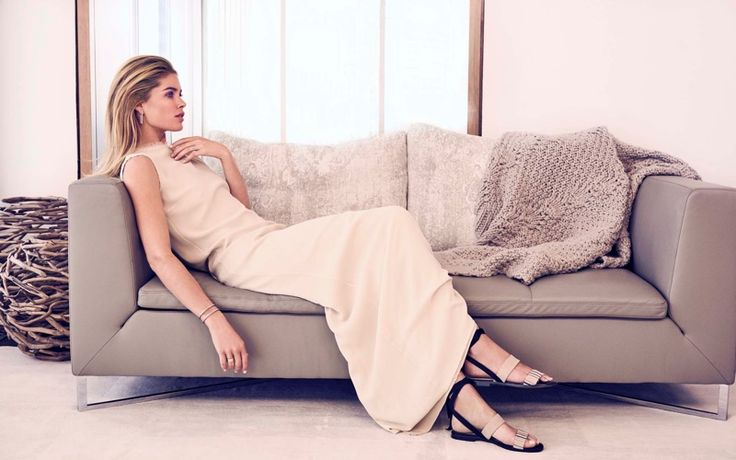 Lounging on a coach, Doutzen Kroes wears The Row dress with Alexandre Birman sandals for Bloomberg Pursuits Magazine November 2016 Issue