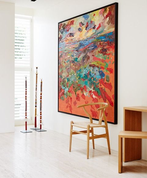 large red green and blue abstract painting by wooden chair | oversized artwork in white room | interior design