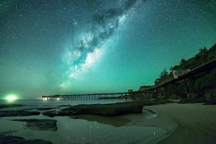 Milky Way over Catherine hills bay, Australia. The Milky Way wasn't always as it is today, a beautiful barred spiral. It became its current size and shape by eating up other galaxies. Photo by: unknown