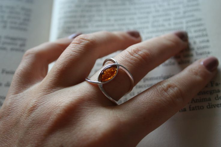 Grande simbolo dell'infinito piegato per avvolgere con raffinatezza il tuo dito. Una montatura insolita con la pietra d'ambra tagliata a marquise. Il colore e la luminosità dell'Ambra Baltica accrescono la bellezza di questo gioiello.