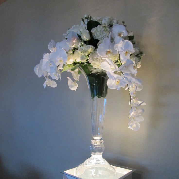 A tall arrangement with roses and Pahalenopsis Orchids