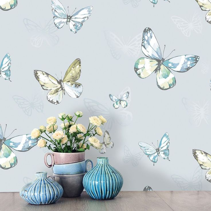 Holden Amelia Butterflies Wallpaper - Blue / Teal 98871  This stunning Amelia Butterflies Wallpaper features a collection of beautiful butterflies in tones of blue, teal and green, with silver gel glitter highlights. This is set on a pale blue background patterned with shimmering mica butterfly silhouettes. Easy to apply, this high quality wallpaper will look great when used to decorate a whole room or to create a feature wall. Beautiful butterfly themed wallpaper Features glitter and mi...