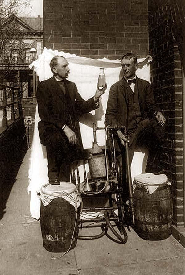 Moonshiners Here for your perusal is a collectible photograph of Two men standing outdoors with small still, one of them holding up bottle of liquor. It was created in between 1921 and 1932.
