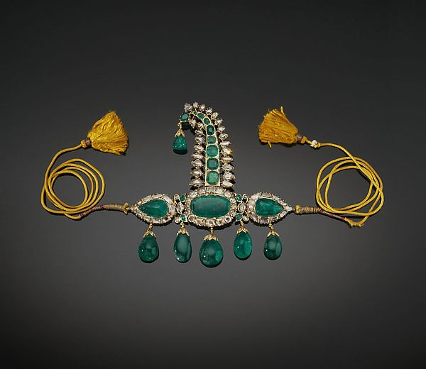 Turban Ornament (sarpesh) Object Name: Sarpesh with Emeralds Date: ca. 1900 Geography: South India, probably Hyderabad Medium: Gold, set with emeralds and diamonds Dimensions: H. 4 7/8 in. (12.4 cm) W. 4 7/8 in. (12.4 cm) Classification: Jewelry Credit Line: The Al-Thani Collection