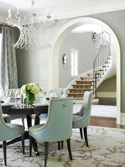 Dining room. Round table. Geometric circle window treatment panels. Blue gray grasscloth wallpaper.  Traditional Home