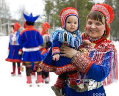 Samisk kvinne bærer et lite barn