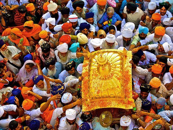 India - Sikhs reach to touch a chest containing a copy of their holy book, the Guru Granth Sahib, as it's carried into Sachkhand Sri Hazur Sahib, a temple in Nanded, during the 300th-anniversary celebration of the book's consecration. Sikhs also mark the anniversaries of the passing of their religion's gurus.