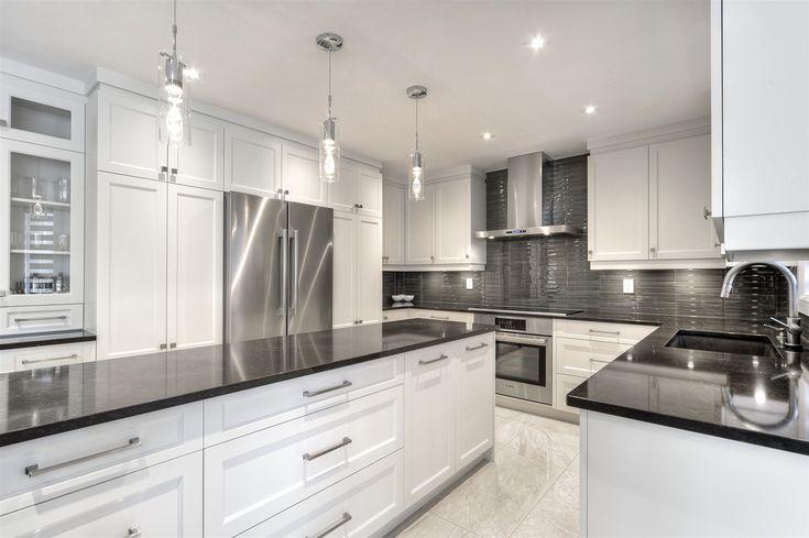 Une cuisine entièrement rénovée de style moderne, des armoires de cuisine haut de gamme MDF en un seul morceau, des comptoirs de quartz faciles d'entretien, pour un style épuré, fonctionnel et robuste.