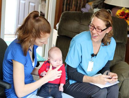 In this photo, the nurse is providing her service to a family with an infant.  (CHN considers the family as the unit of service)