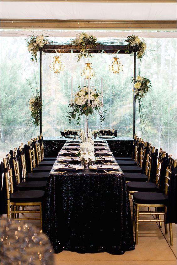 Recepción de bodas en negro y dorado bajo una carpa transparente en un jardín.