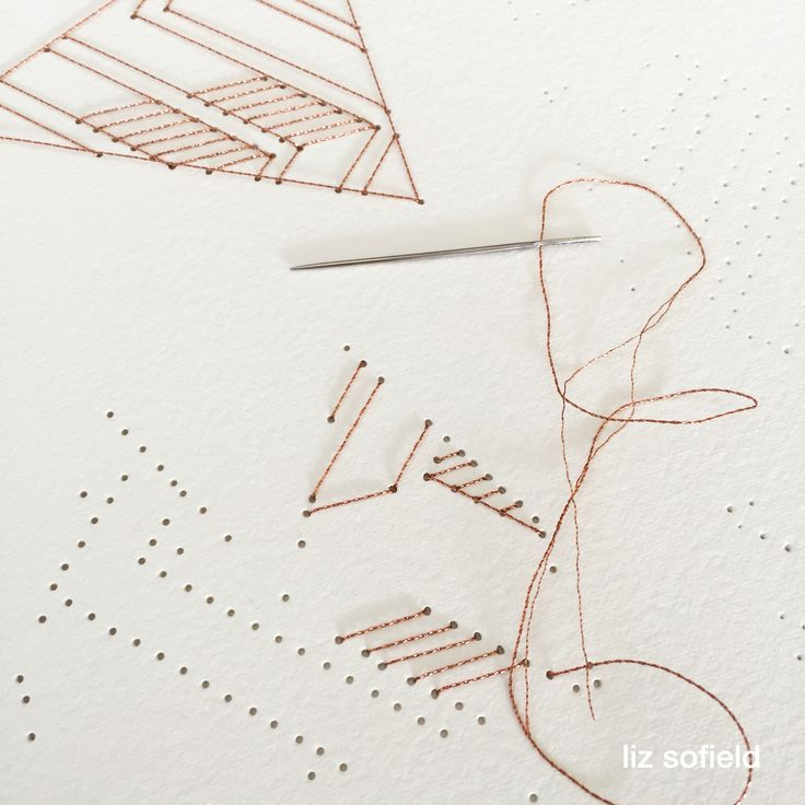 Hand stitching letters on paper using copper thread.