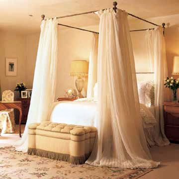 Sheer Elegance  This glamorous canopy bed takes advantage of the room's soaring ceiling. The wrap of sheer curtains turns the bed into a cozy island in the clouds. The subtly iridescent fabric sparkles in the shifting light.