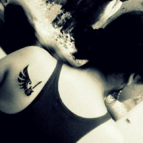 A simple and subtle guitar tattoo on the small part of the back. The all black and minimalist style of the one winged guitar makes it look truly beautiful and enchanting.