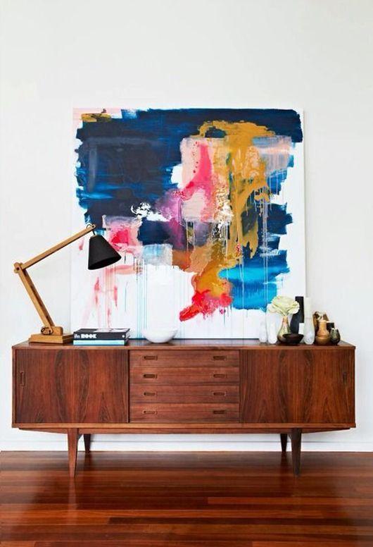 Un mix ben fatto: il mobile vintage in legno ( stessa tonalità del parquet) abbinato alla tela astratta di arte moderna.