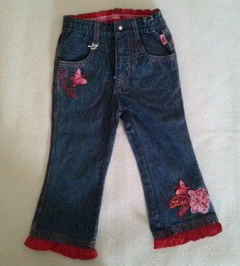 Pantalone jeans in denim con chiusura zip,elastico in vita e bottone gioiello,logo ciondolo in metallo e scritta ricamo PAMPOLINA. Applicazioni ricamo sulle gambe con pailettes e perline di colore rosso. .Fondo gamba con arricciatura in cotone rosso. Da etichetta veste tg .86 (12-18 mesi).