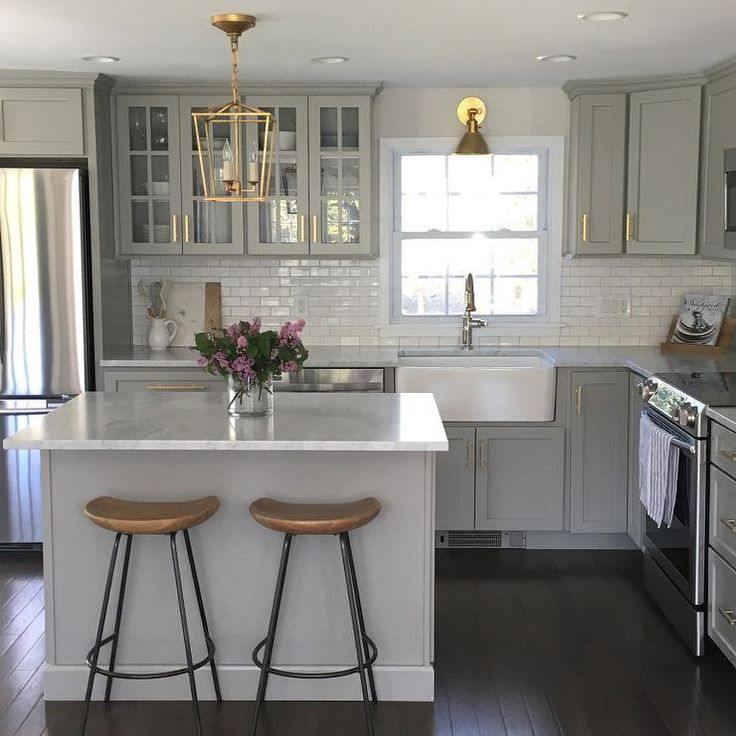 Gray kitchen features gray shaker cabinets adorned with brass pulls by  Lewis Dolan paired with honed  Gray And White KitchenSmall ...