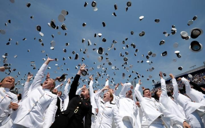 Graduates toss their hats high in the air at the conclusion of their graduation and commissioning ceremony at the U.S. Naval Academy in Annapolis, Maryland
