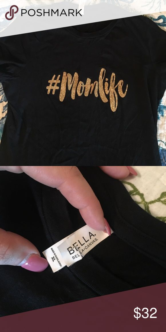 #MomLife Top Bought this at a local boutique, size XL but it runs a little small in my opinion. Has a fitted fit. I paid $35 for it, only wore it one time. Has super pretty gold glitter letters that say #momlife. Perfect Mothers Day present! ⭐️Buy two or more items, you get 30% off your bundle!⭐️ Open to offers on single items! Bella Canvas Tops Tees - Short Sleeve