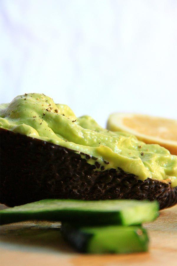 Maionese crudista di avocado servita nella metà di un avocado svuotato, accanto delle fette di cetriolo per accompagnamento e mezzo limone