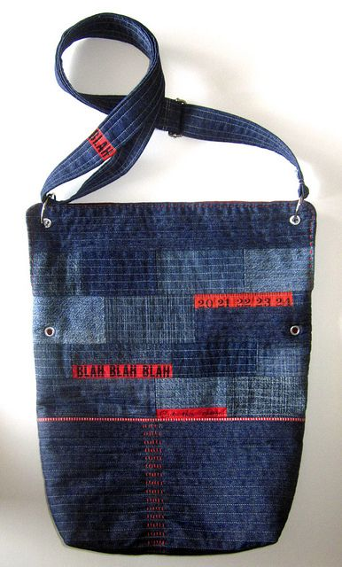 Denim (different shades) + measuring tape (fabric?) + grommets + (is that embroidery in red along the bottom center?) = gorgeous denim tote :)