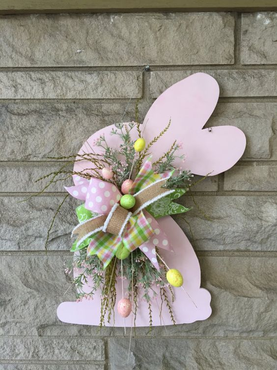 """This easter door hanger is made of wood. Bunny measures 22 inches Has a mix of ribbon,greenery and Easter eggs. ** ribbon and greenery may vary depending on stock, but will still be super cute! This new design will have your door the envy of the neighborhood! We are proud to say """""""