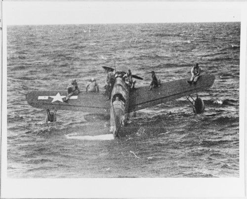 """Vought OS2U Kingfisher floatplane, from USS North Carolina (BB-55) off Truk with nine aviators on board, awaiting rescue by USS Tang (SS-306), 1 May 1944. The plane had landed inside Truk lagoon to recover downed airmen. Unable to take off with such a load, it then taxied out to Tang, which was serving as lifeguard submarine during the 29 April-1 May carrier strikes on Truk.""  (NHHC: 80-G-227991)"