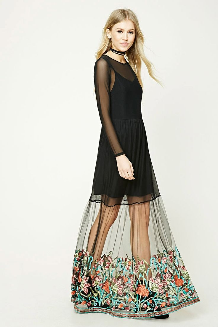 A sheer mesh knit maxi dress featuring a knit mini cami dress underlay, a layered mesh skirt with floral embroidery at the hem, a round neckline, long sleeves, and a buttoned keyhole back.