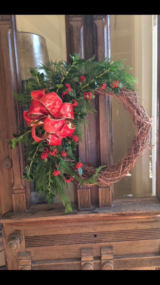 Christmas wreath made of grape vines and other greenery and red berries.