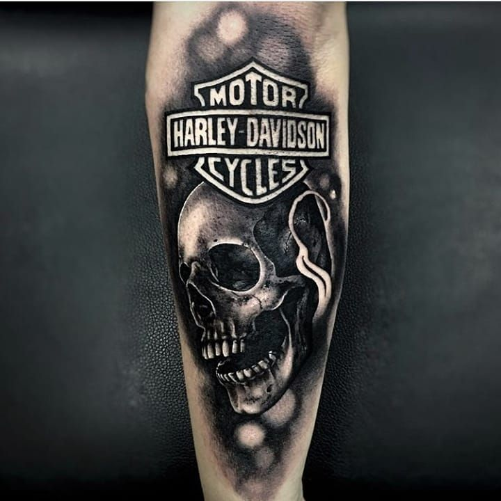 Realist Black And Grey Harley Davidson Logo And Skull Tattoo Done By Our Artist Guizo Call Us Today Dream Catcher Tattoo Design Tattoos Lower Back Tattoos