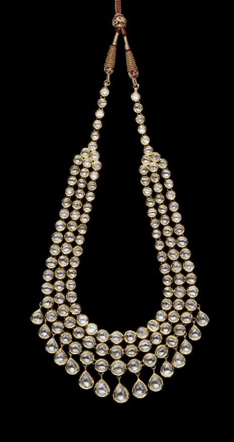 A diamond-set enamelled gold Necklace   India, Jaipur, 20th century  comprising three rows of circular diamonds set in gold, terminating in a single row of diamonds, larger teardrop shaped diamonds suspended below, verso enamelled in polychrome with floral design   23 cm. long