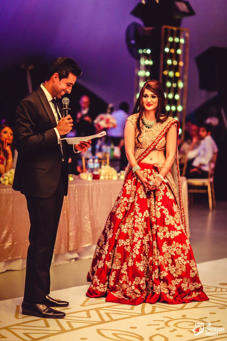 Groom Reading Out Vows to Bride in Red and Gold Lehenga
