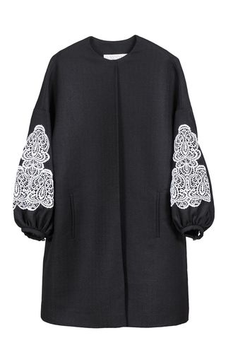 This **Yanina** collarless coat features a bishop sleeve and contrast embroidered detail from elbow to wrist.