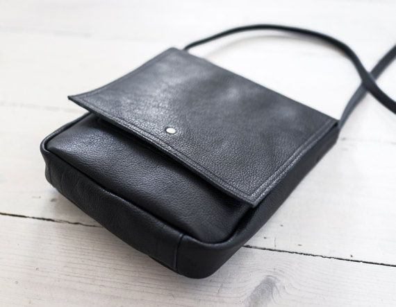 A small, minimal crossbody bag. Made of black thick leather. With one pockets inside. Close with snap. No lining. Dimesions: height: 23 cm/ 9 witdht: 20 cm/ 8,2 depth: 4 cm/ 1,5 strap : 128 cm/ 50,5   For these bag, please expect 1 week for your item to be made and prepared for shipment!  Standard delivery time:  European union: 4 - 10 days  Europe (not EU): 7 - 14 days  U.S.A., Canada: 10 - 20 days  Australia, South America, Asia, India, North Africa: 1 - 3 weeks  We sen...