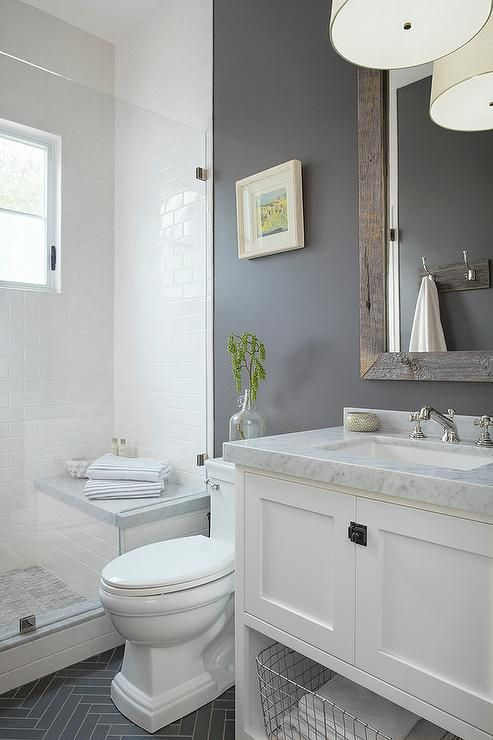Gray and white bathroom features a white washstand fitted with a shelf holding a metal bin and a carrera marble countertop holding a sink with a polished nickel cross handle faucet beneath a reclaimed wood beveled vanity mirror mounted on a gray wall lit by a white drum pendant.
