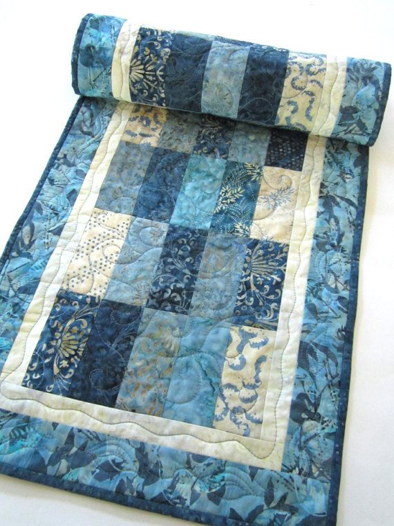 Blue Batik Quilted Table Runner 16 x 60 This table runner is made using a variety of blue fabrics. This runner will be a beautiful setting for your table. This runner would also be a wonderful gift to give someone. This table runner is 16 x 60. The fabric is 100% cotton. Warm 100