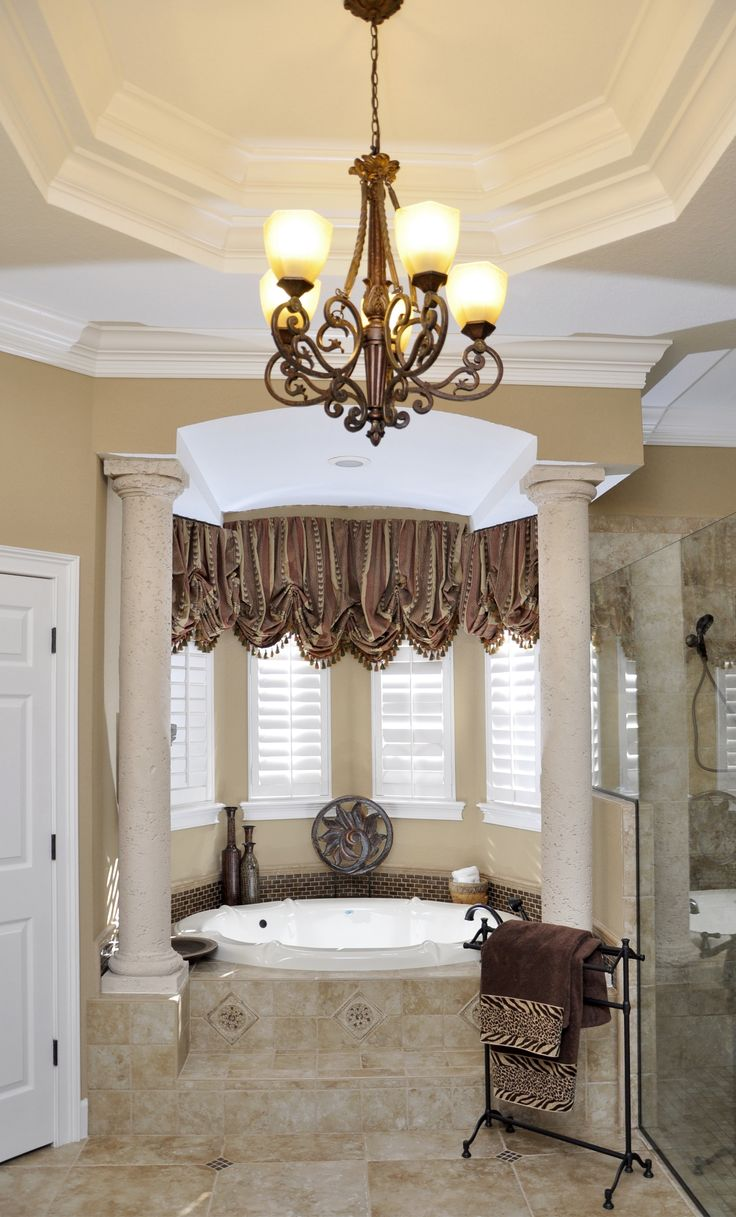 chandelier in classic neutral bathroom with columns, frameless shower, high ceilings, accent molding... by the BEST custom home builder / remodeler in central Florida | www.allinconstruction.com