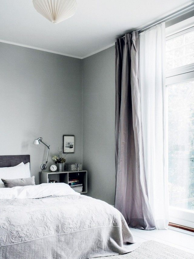Bedroom with gray walls, cozy bedding, and a lantern