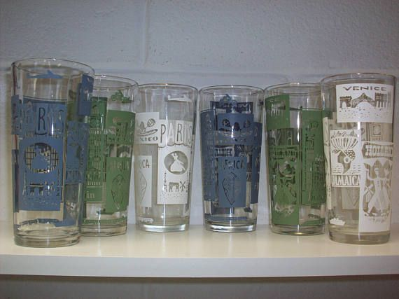 This set of 6 mid century drinking glasses feature cool travel poster themes and modes of transportation. Maybe you need them for your retro kitchen or to add to your bar accessories.  Each hefty tumbler measures 5 1/2 tall. They are in excellent condition with no chips or fade to the patterns. Destinations shown are Paris, Britain, Venice, Holland, Africa, Jamaica and Mexico. 2 are olive green, 2 are blue and 2 are bright white.  This set is heavy. The shipping price listed is for the W...