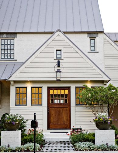 painted brick with clapboard and a mix of the metal roof.Add a front door!!